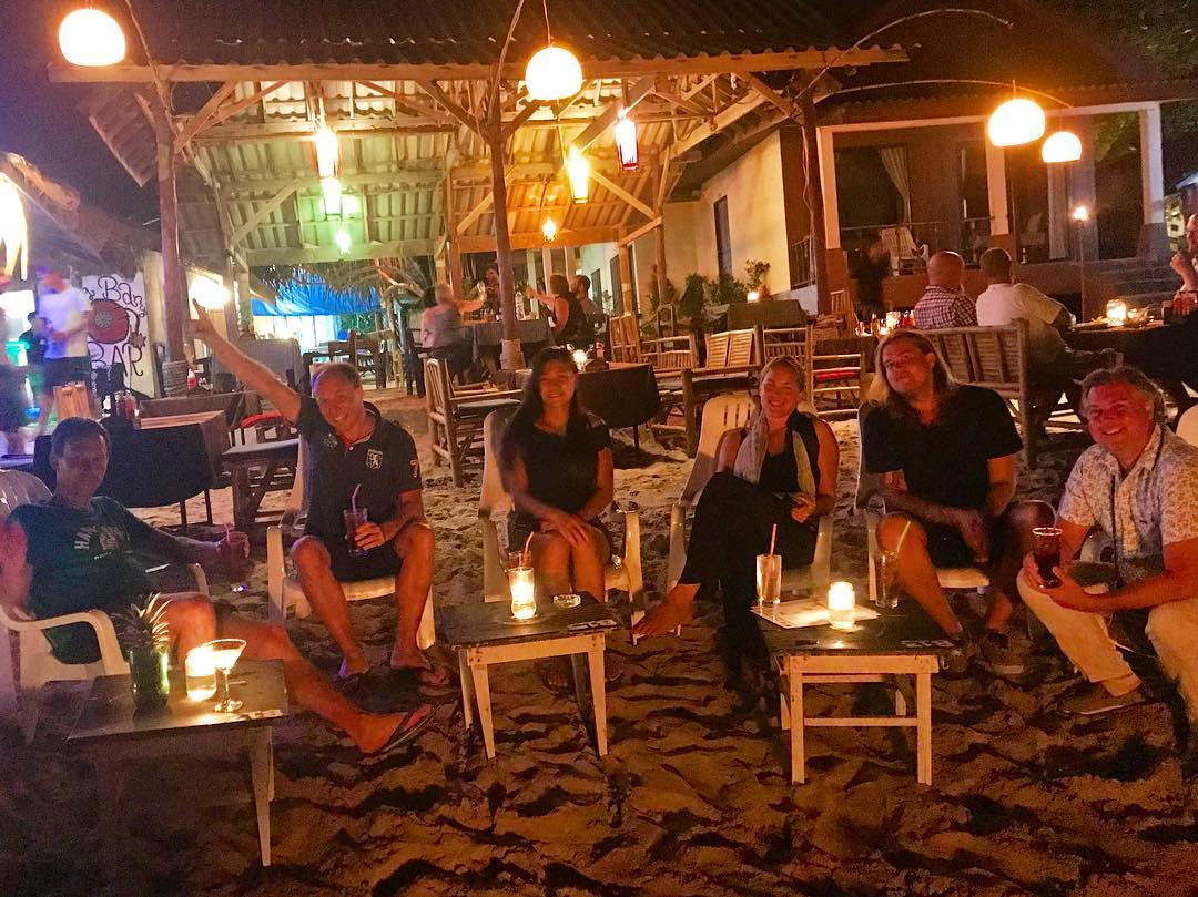 people are sitting on the beach in front of the Big Bang Bar Koh Lanta