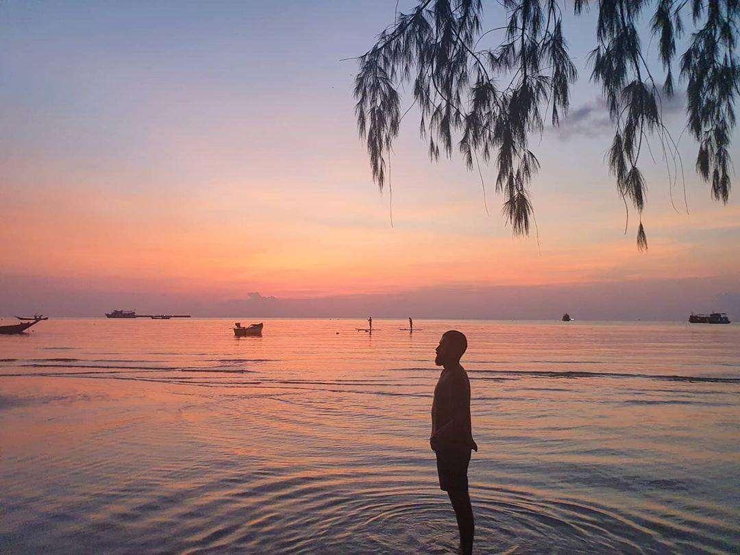 Iemand staat in de zee van Koh Lanta tijdens de avondschemering