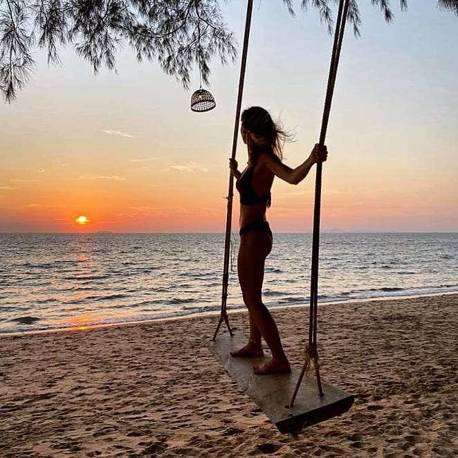 Meisje in bikini staand op een schommel op een strand van Koh Lanta terwijl de zon ondergaat
