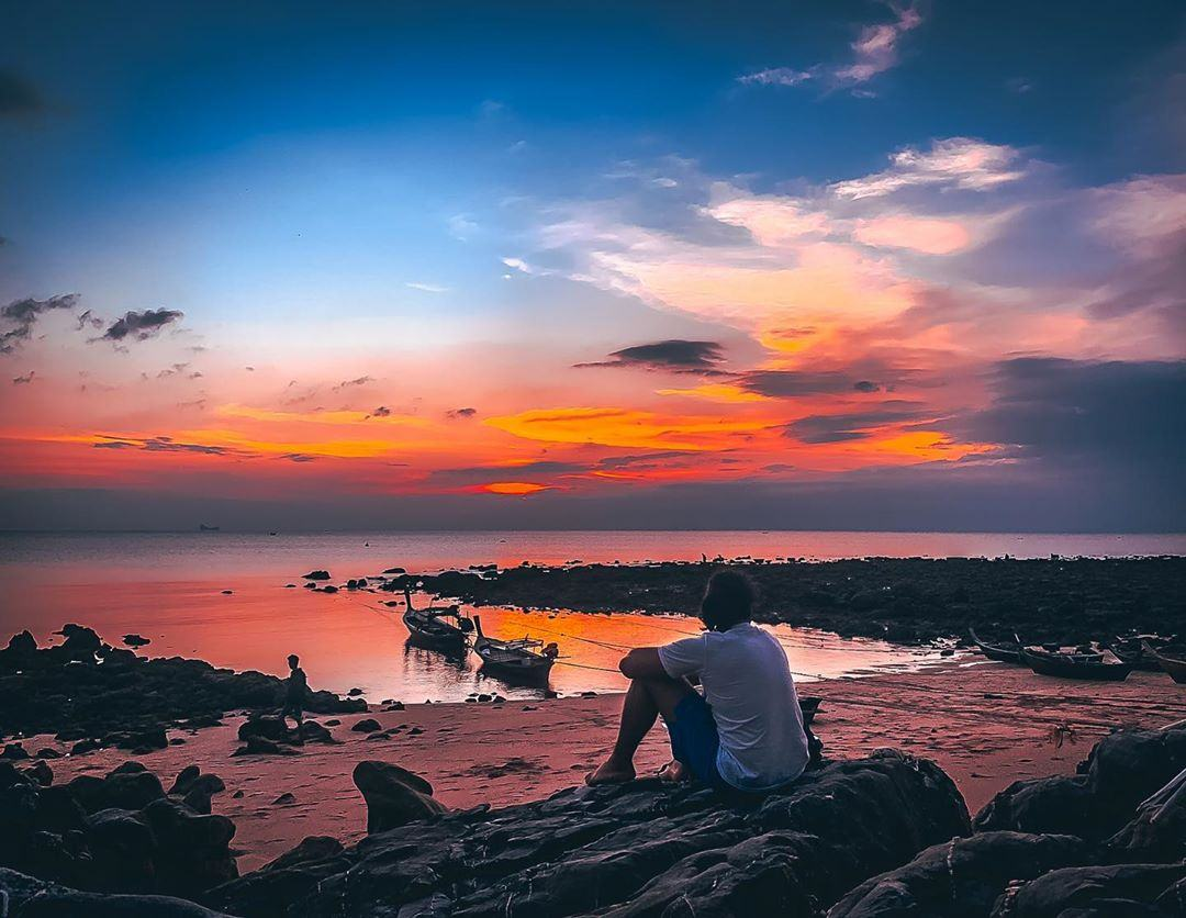 Sitting on a rock and watching the sunset on Koh Lanta, Thailand