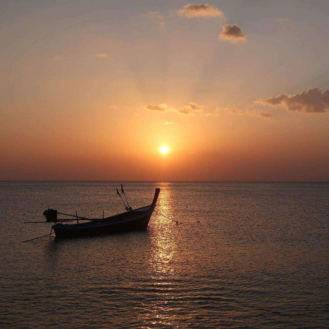 Longtailbootje op zee tijdens Koh Lanta's zonsondergang