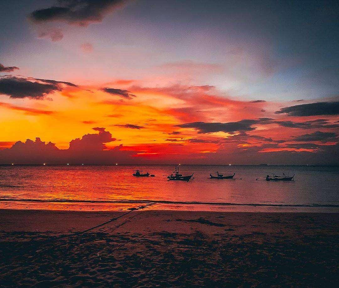 Longtailbootjes op zee tijdens Koh Lanta's zonsondergang