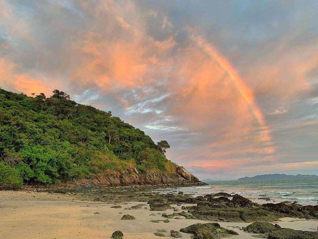 Regenboog boven een strand van Koh Lanta