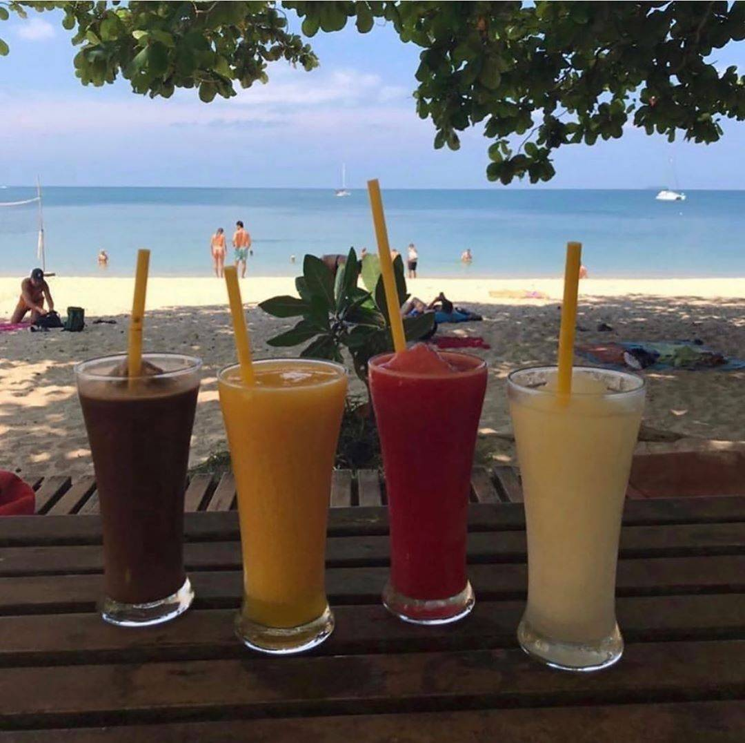 Four different kinds of fruit shakes with picked out on the beach