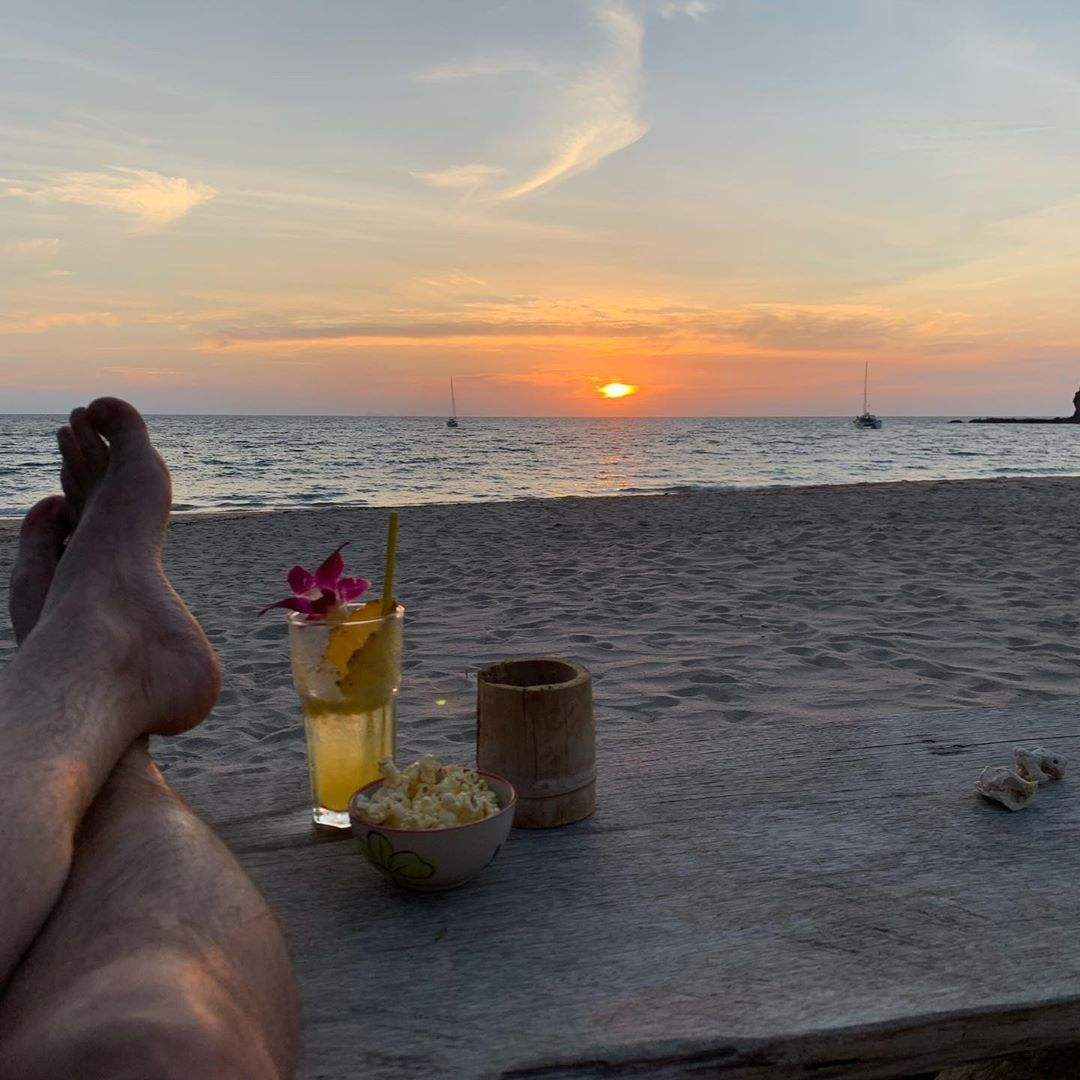 hanging out on the beach of Koh Lanta with bare feet and a cocktail