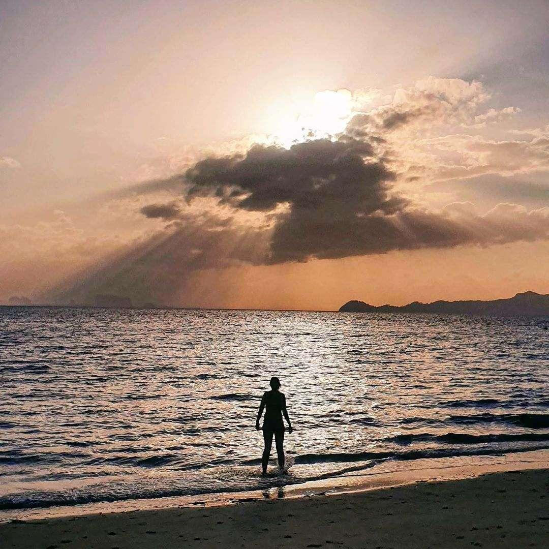 Man op het strand van Koh Kradan tijdens zonsondergang
