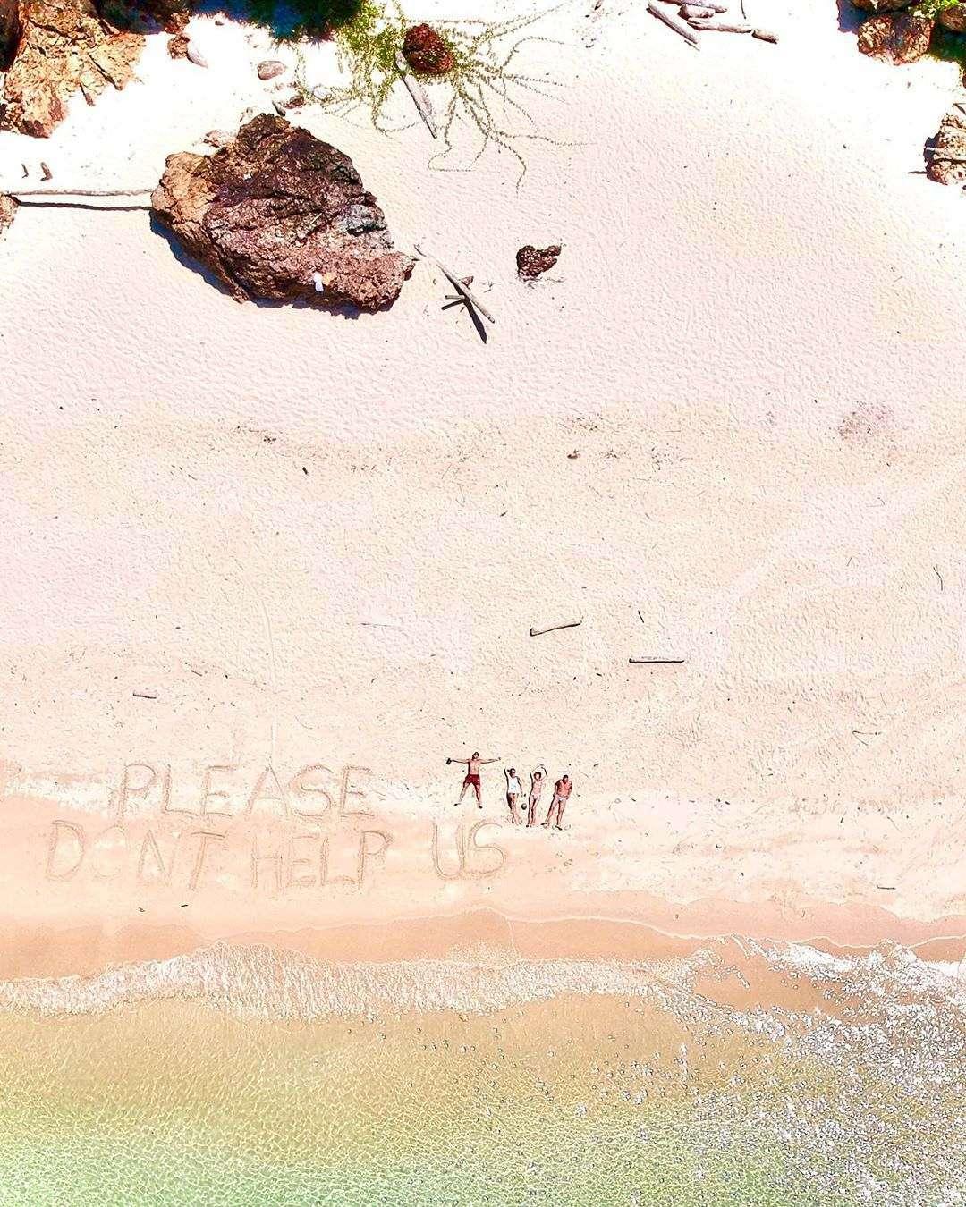 Please don't help us geschreven in het zand van het strand van Koh Kradan gezien vanaf een drone
