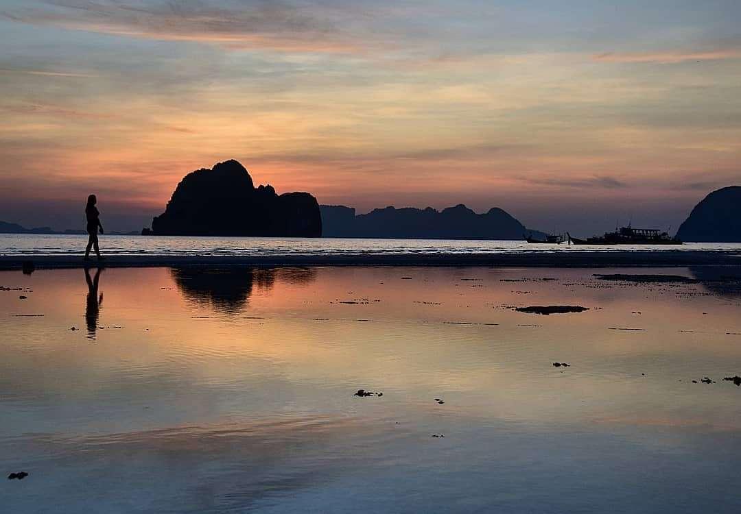 Lopend over het strand tijdens de avond als de zon onder is op Koh Ngai