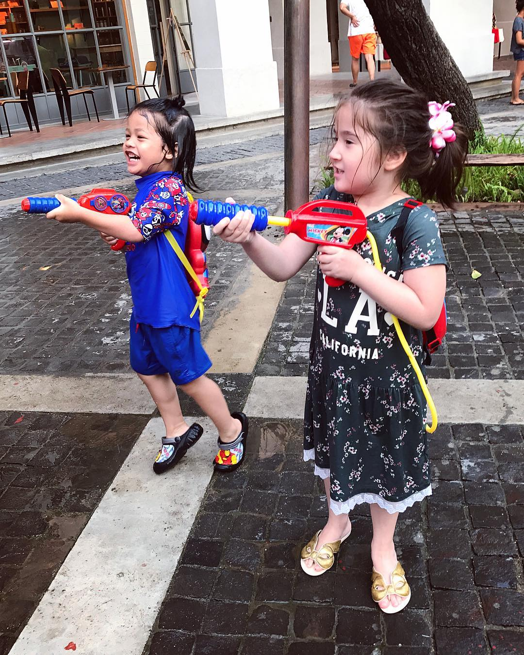 Two young girls with water guns during Songkran in Thailand