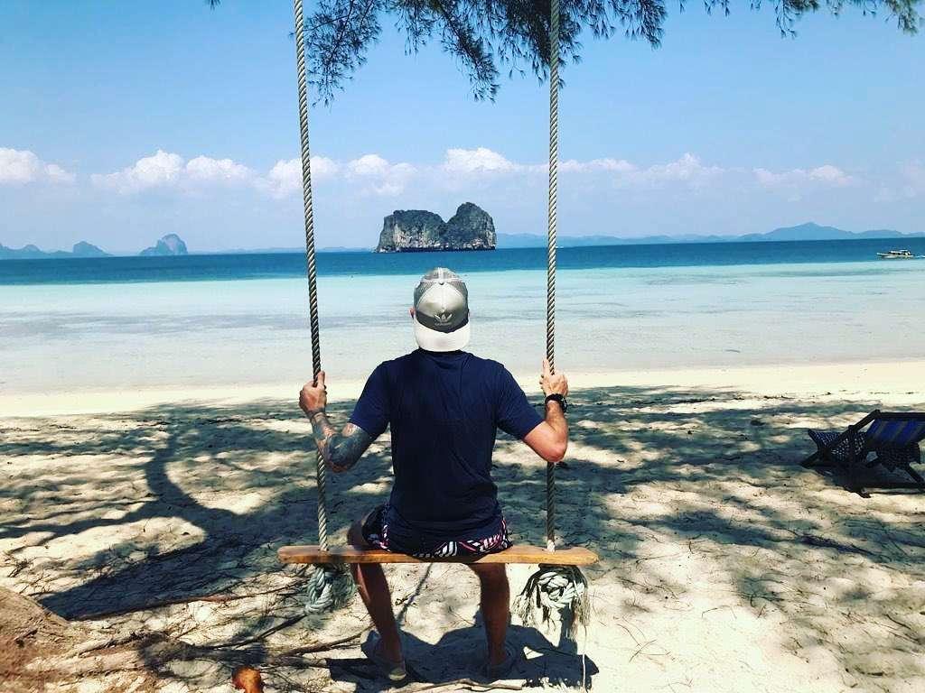 Man op schommel uitkijkend over de Andaman zee voor Koh Kradan