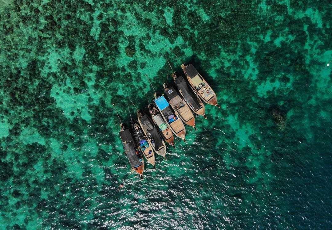 Aantal longtailbootjes in het blauwgroene water van de zee bij Koh Ngai