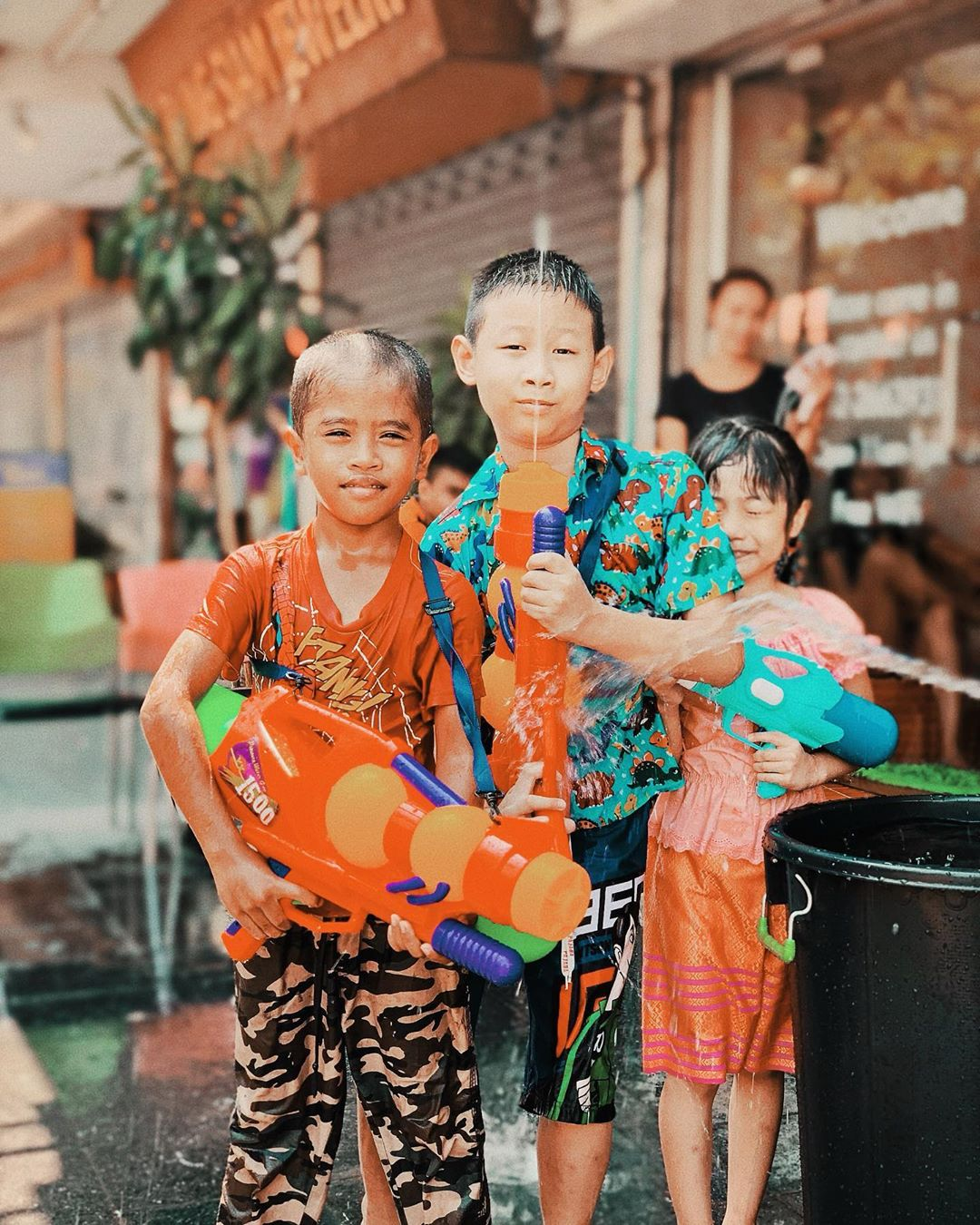 Three little kids with water guns during Songkran in Thailand