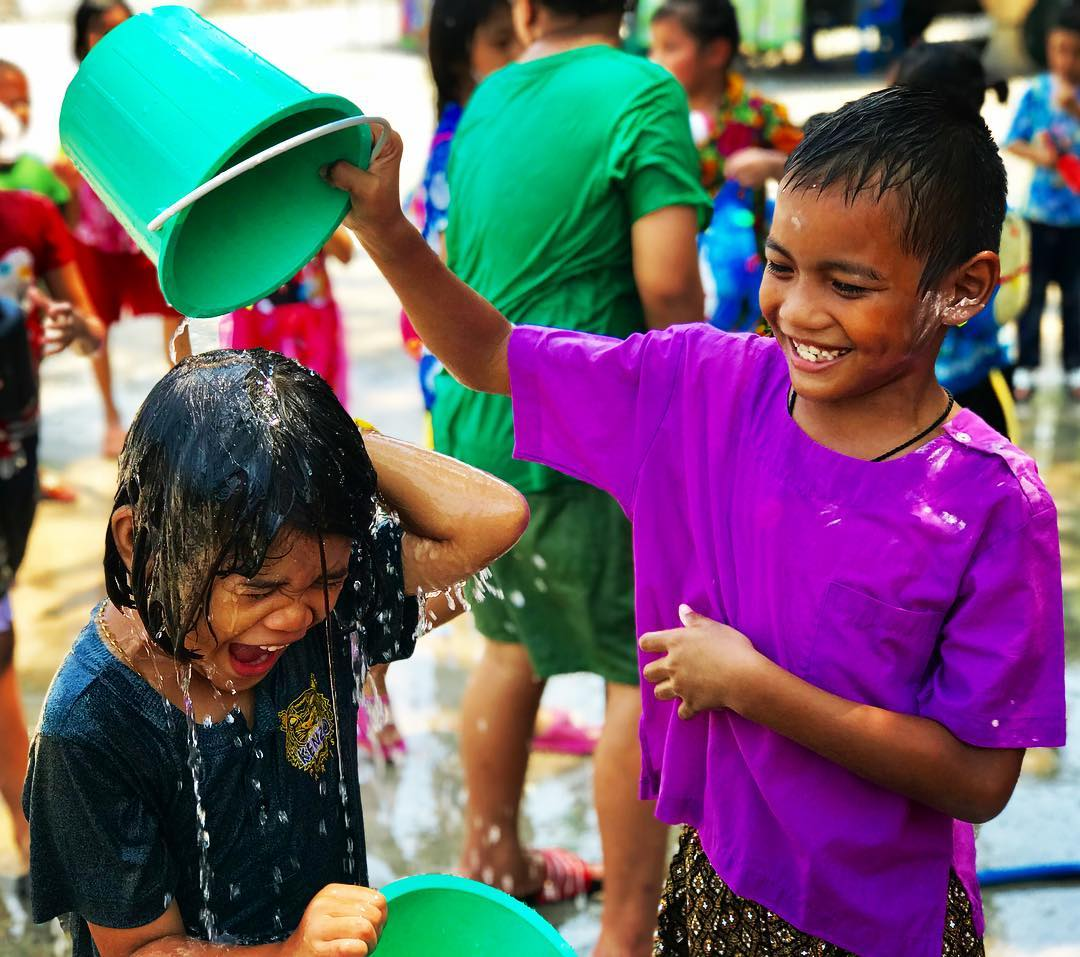Little boy throwing a bucket over little girl during Songkran