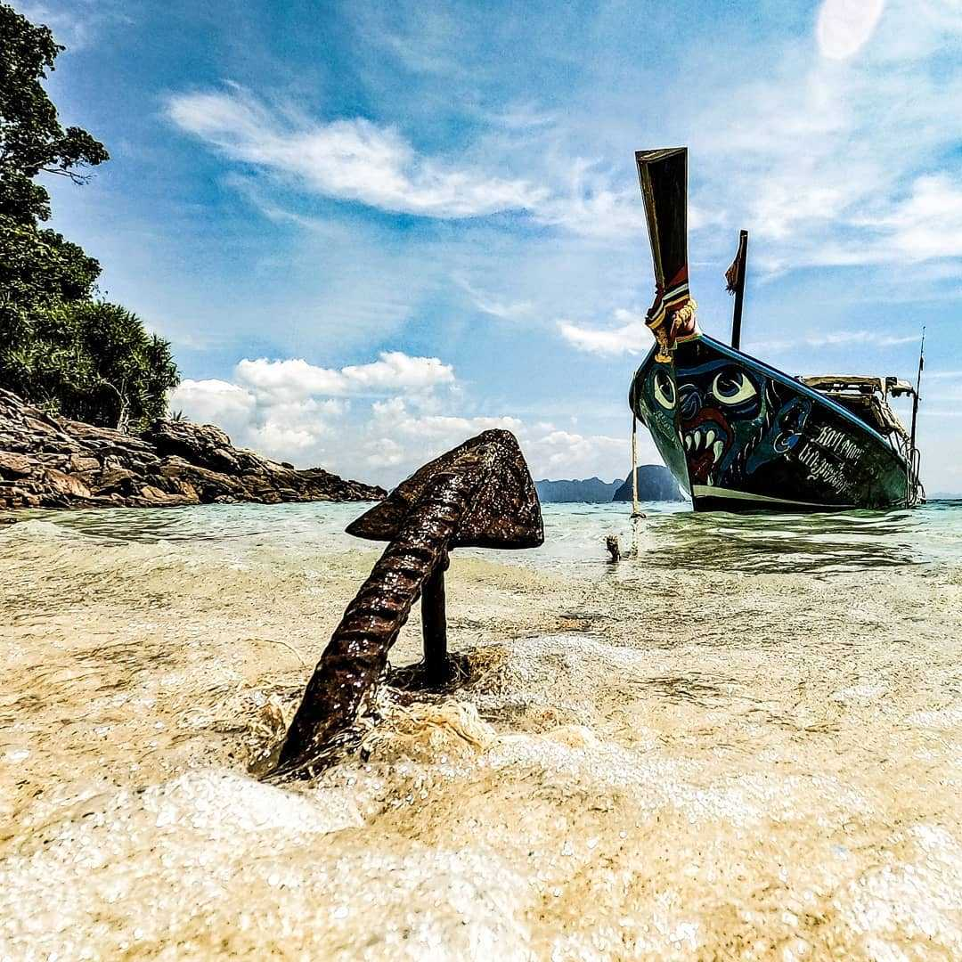 Longtail boat moored with anchor in the sand of Koh Ngai