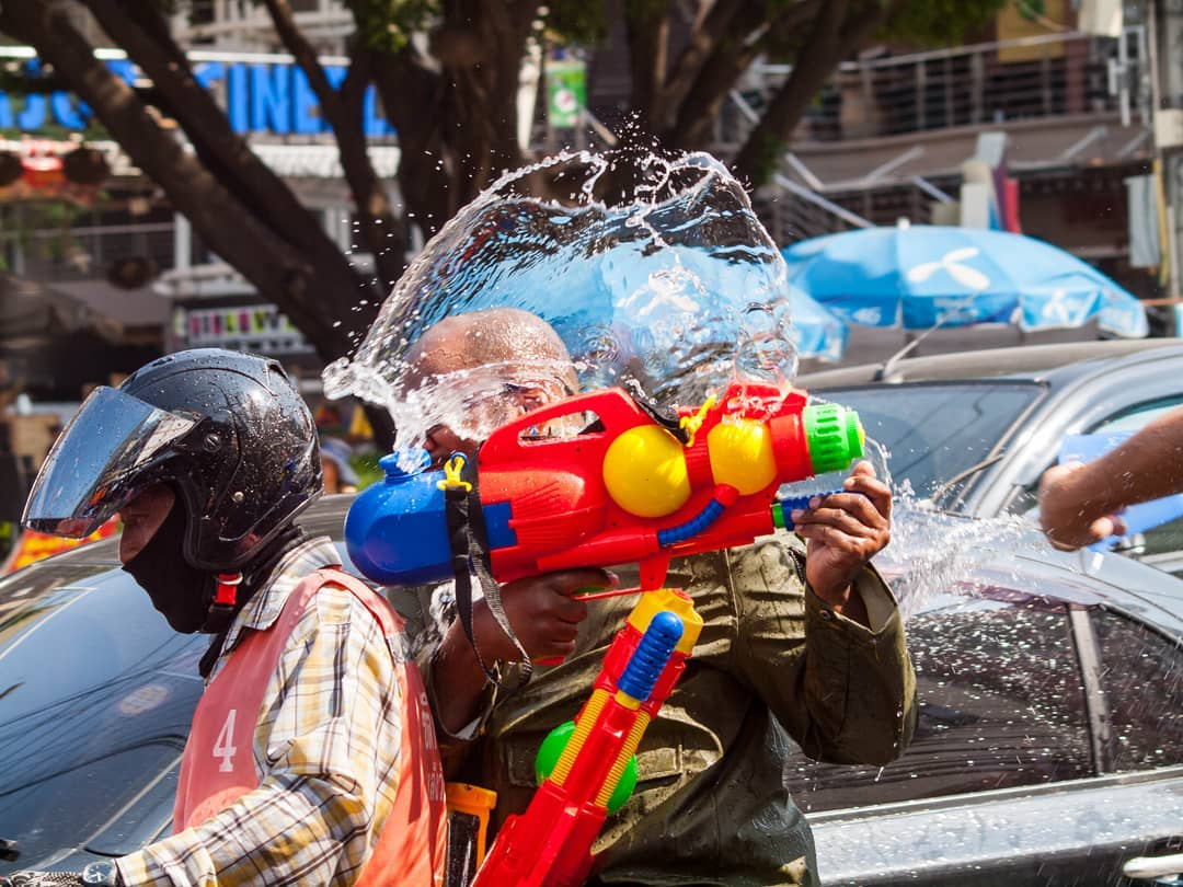 somebody on the back of a motorbike that gets sprayed wet during Songkran