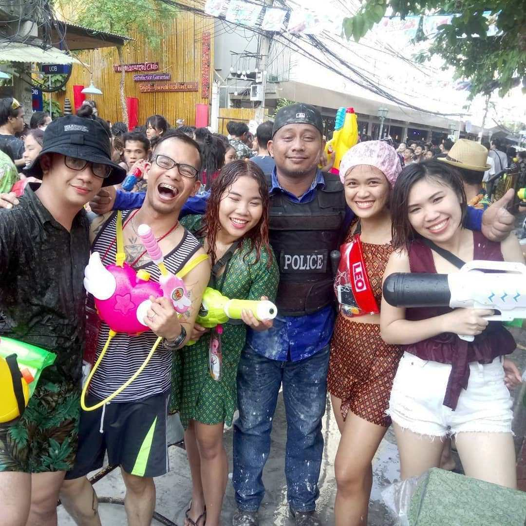 Group of people with a policeman during Songkran in Thailand