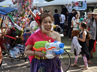 Woman In Traditional Thai Costume With Mega-sized Water Pistol During Songkran In Thailand