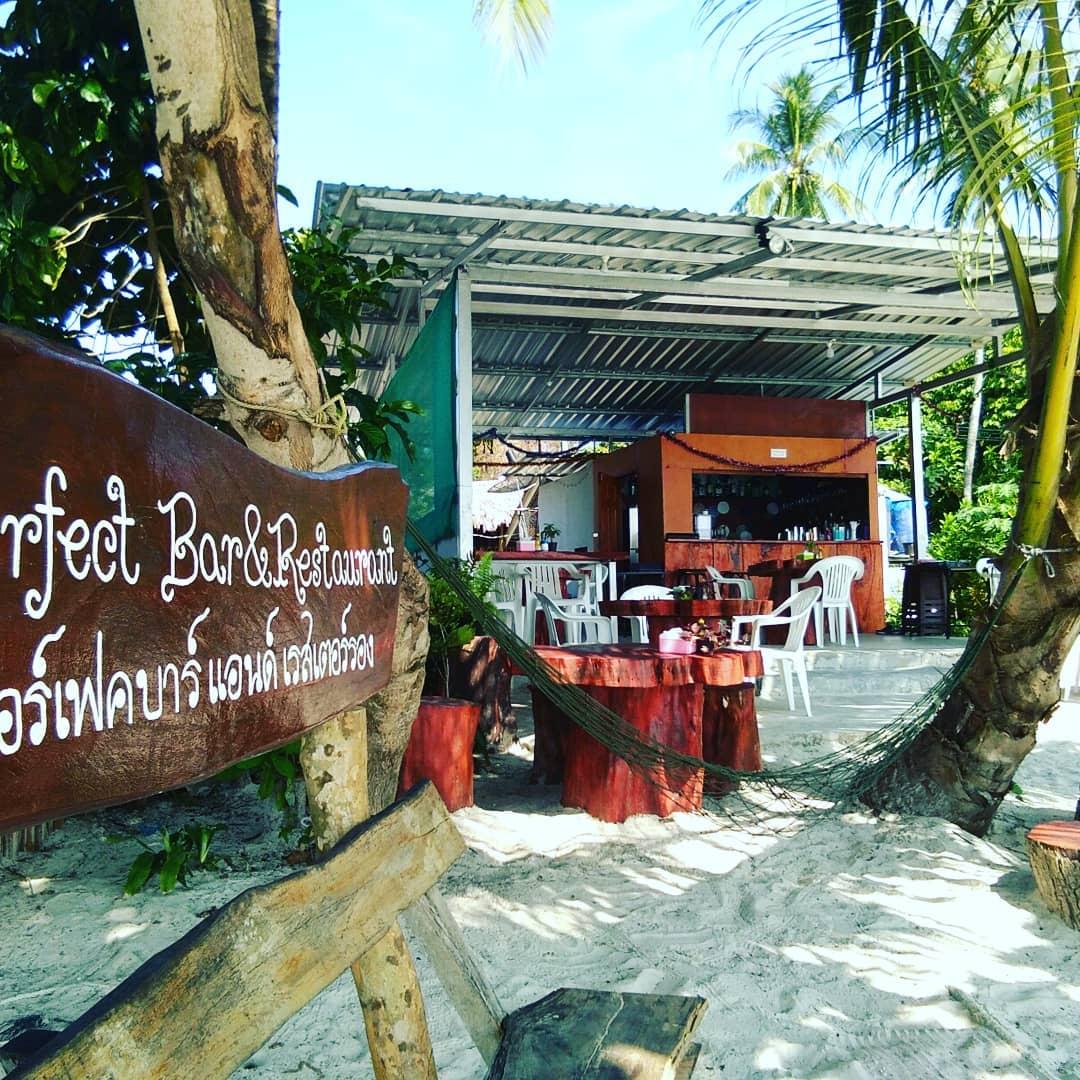Tafeltjes in het zand tussen de palbomen van Perfect Bar and Restaurant Koh Mook