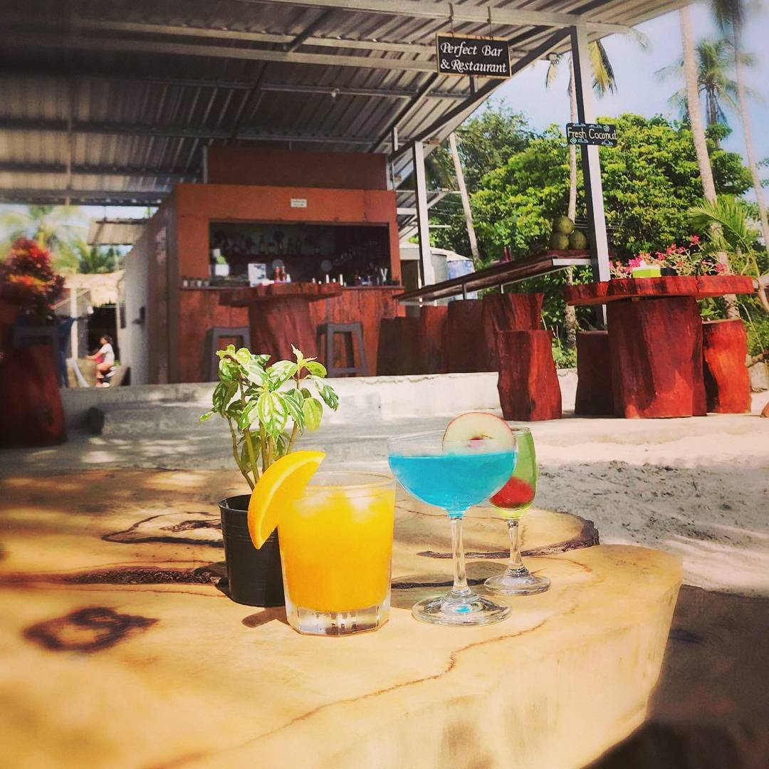 kleurrijke cocktails op een tafel in de zon bij Perfect Bar