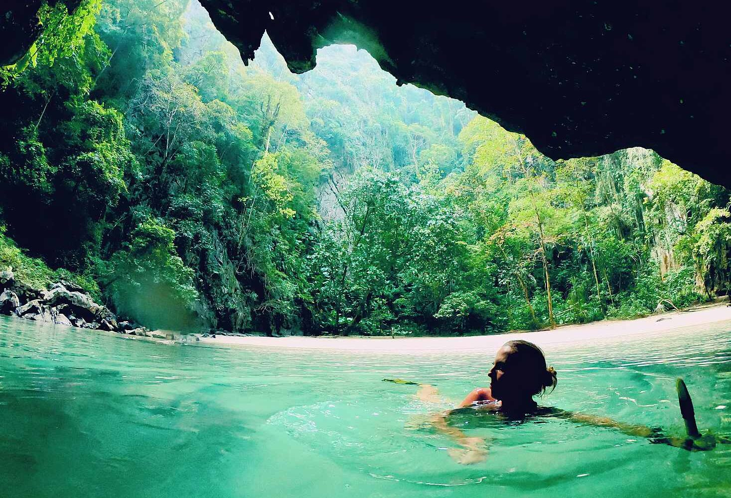 woman swimming in the cave with the Emerald Cave in the background