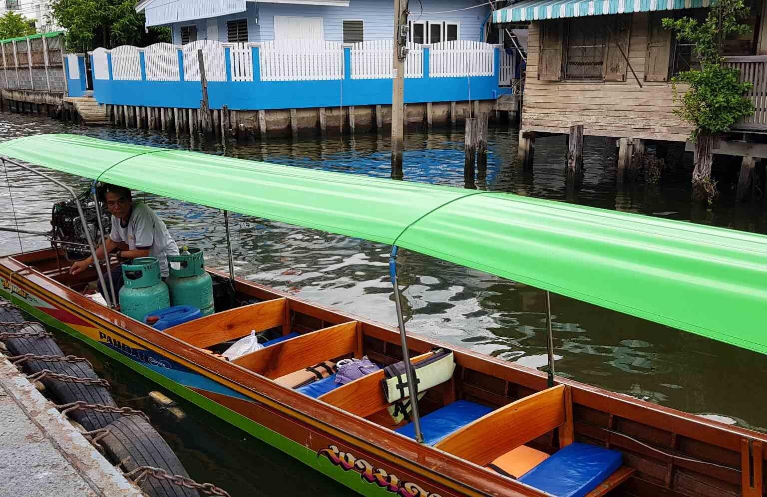 Longtail boot met bestuurder op de rivier van Bangkok