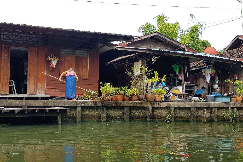 Huis op het water met vrouw die de was doet aan de rivier