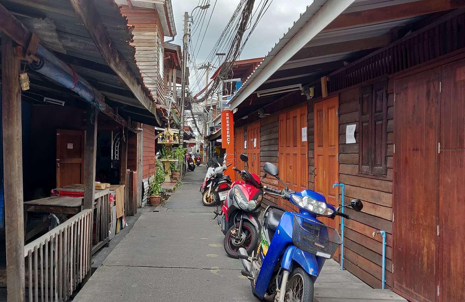 Smal straatje met houtenhuizen in Thonburi