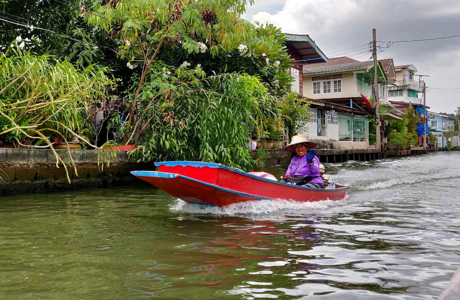 Thaise vrouw zwaait vanuit een voorbij varende longtailboot