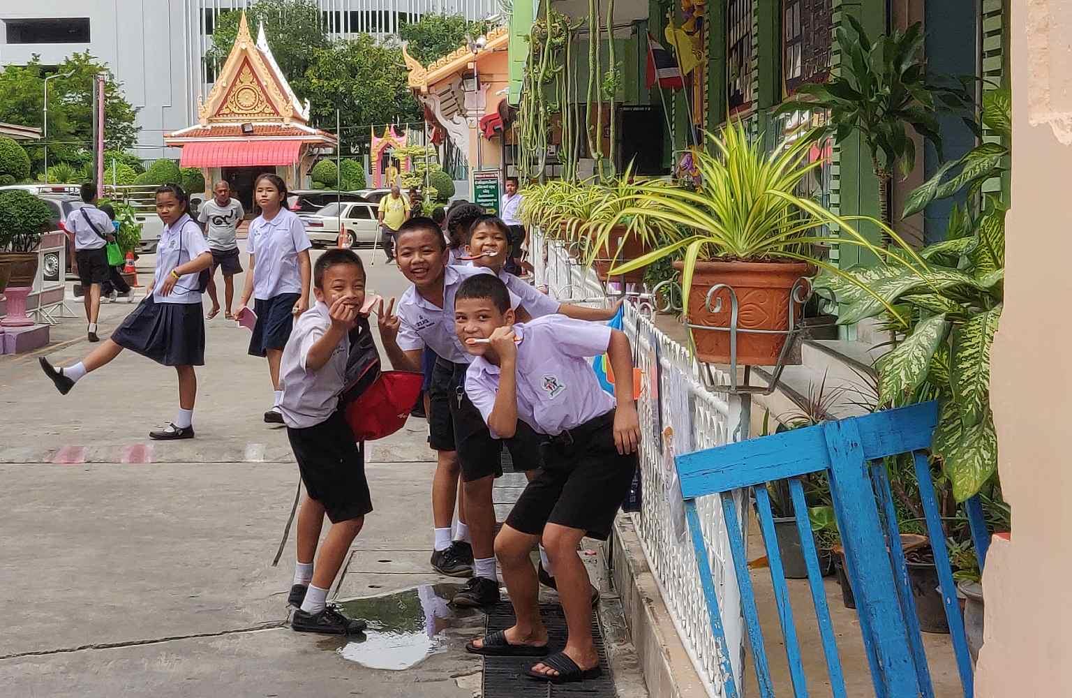 Groepje schoolkinderen poetsen hun tanden op straat.