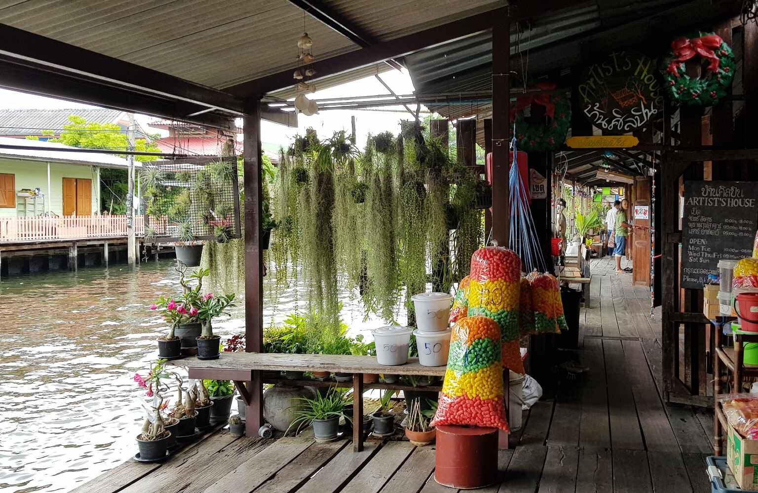 The Artist House, huis met houten vlonders en plantjes aan het water
