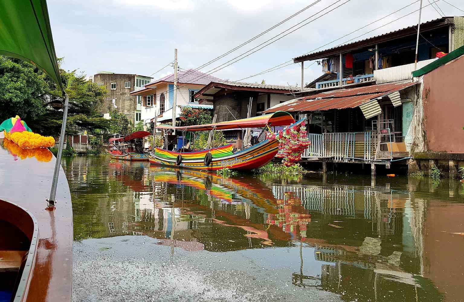 Twee longtailboten kruisen elkaar op de rivier