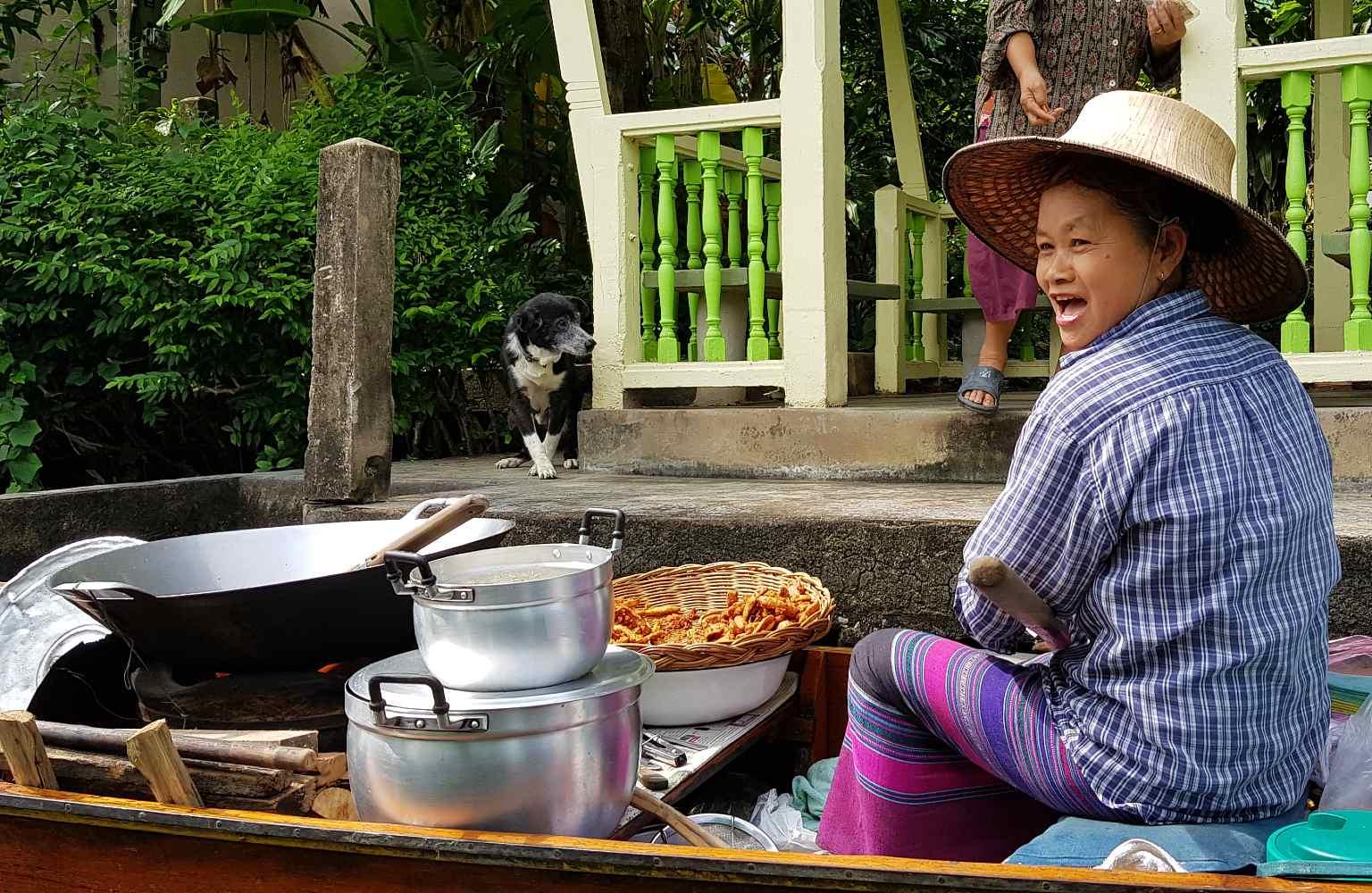 Thaise vrouw verkoopt gebakken banaan vanaf een longtailboot