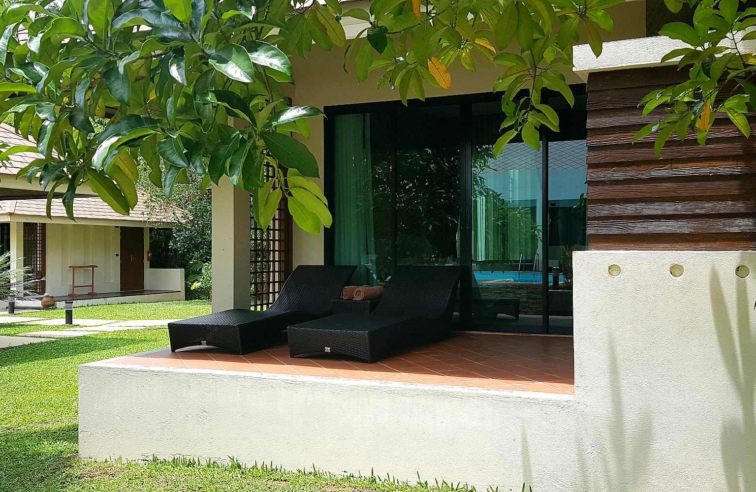 terras met ligbedjes met uitzicht van de Pool View Villa