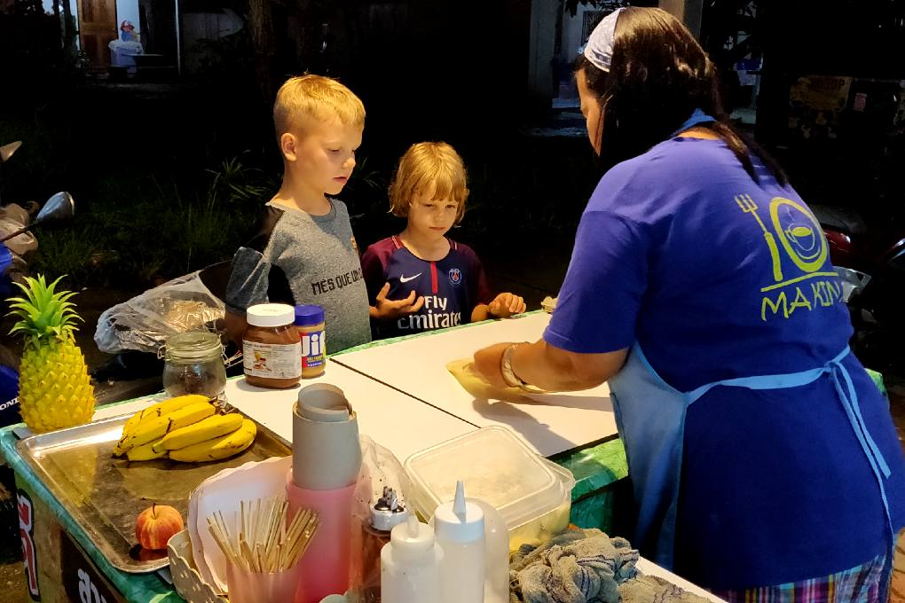 Vrouw bakt roti Pancakes en kinderen kijken toe
