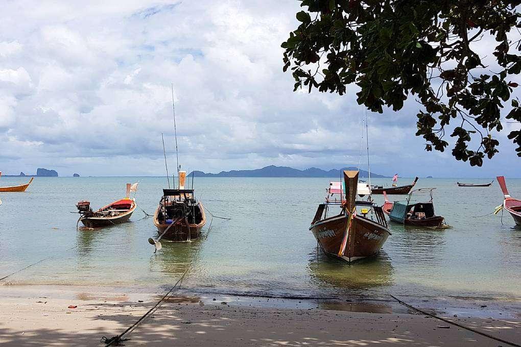Uitzicht op zee en longtailboten vanuit Sugar's coffee and restaurant