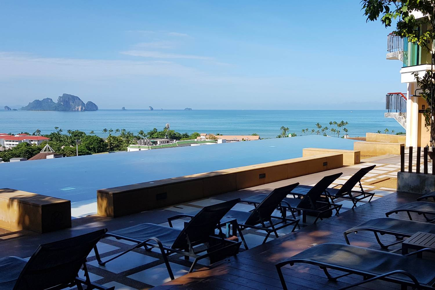 The infinity pool with sunbeds at the Avani Ao Nang Cliff Krabi Resort