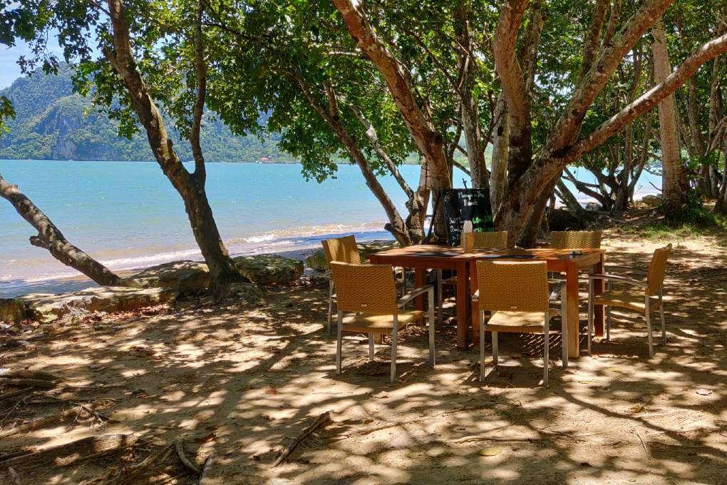 Buiten zitten in de schaduw aan de kust bij de Massaman beef in de Andaman Beach Club