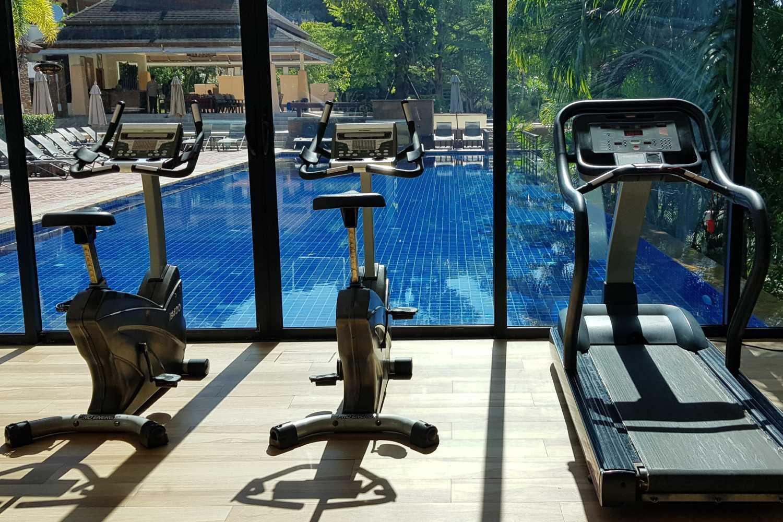 De fitnesszaal die uitkijkt op het zwembad van het Avani Ao Nang Cliff Krabi Resort