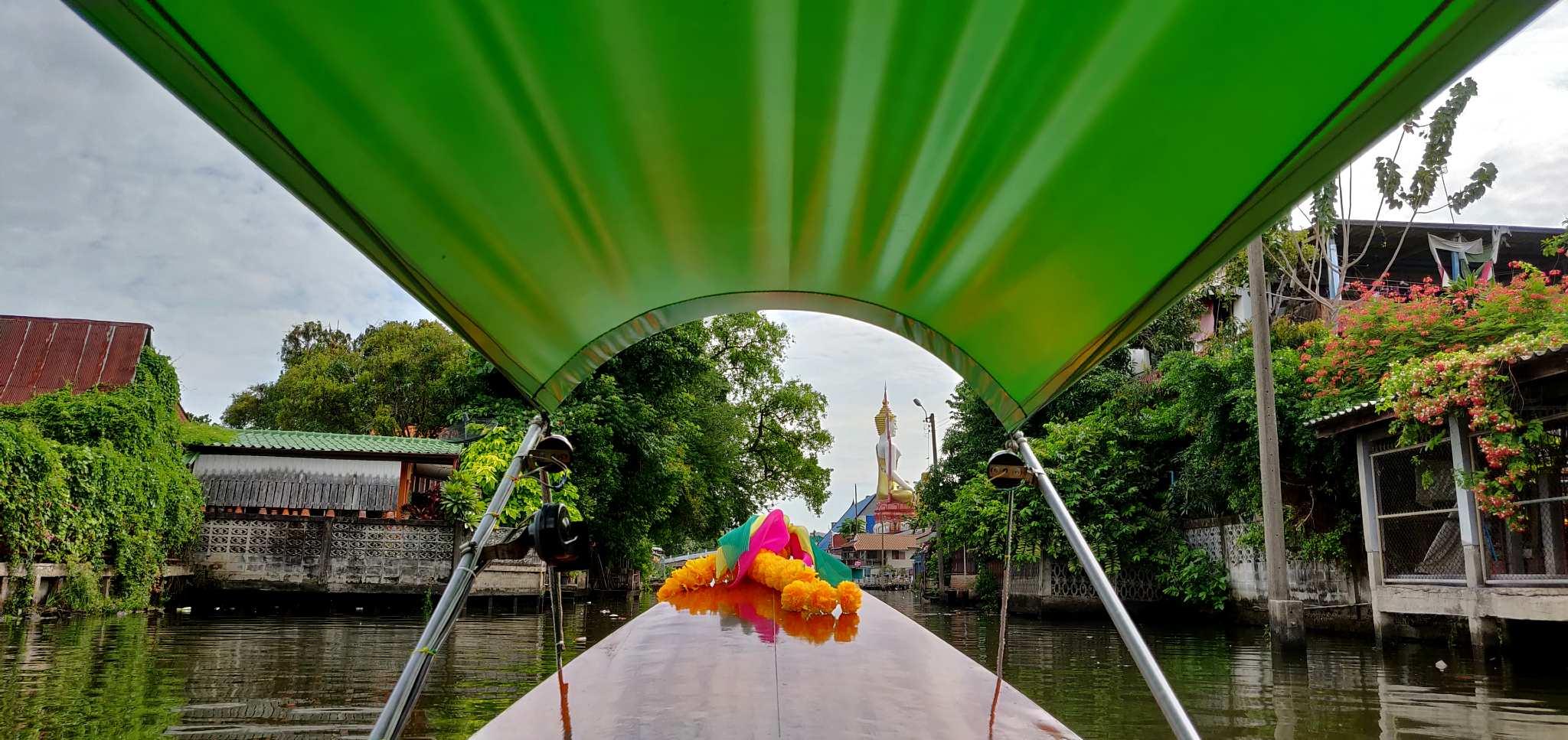 Longtailboot in de kanalen van Bangkok, met een tempel op de achtergrond