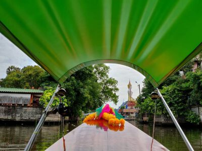 Longtail Boat In The Klongs Of Bangkok, With In The Background A Large Buddha Statue