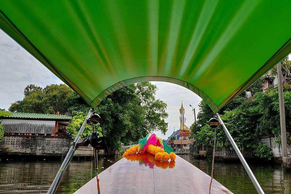 Longtailboot in de Klongs van Bangkok, met op de achtergrond een groot Boeddhabeeld