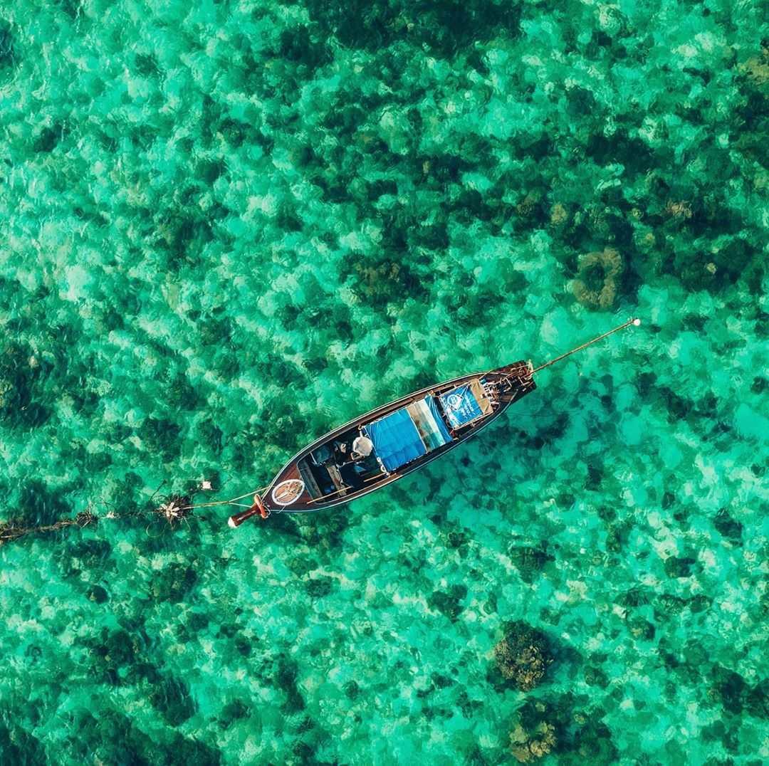 blauwgroene zee met een longtailboot gezien vanaf een drone