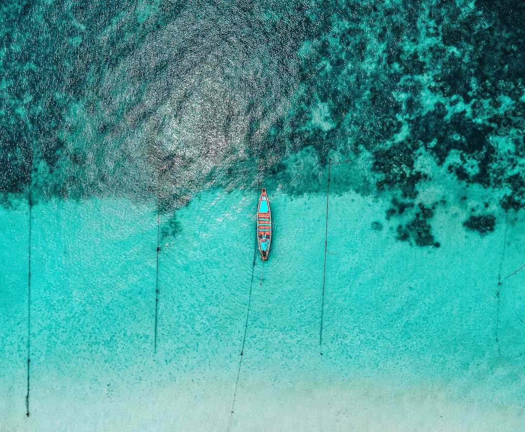 Boat seen from a drone with blue-green water on Koh Tao