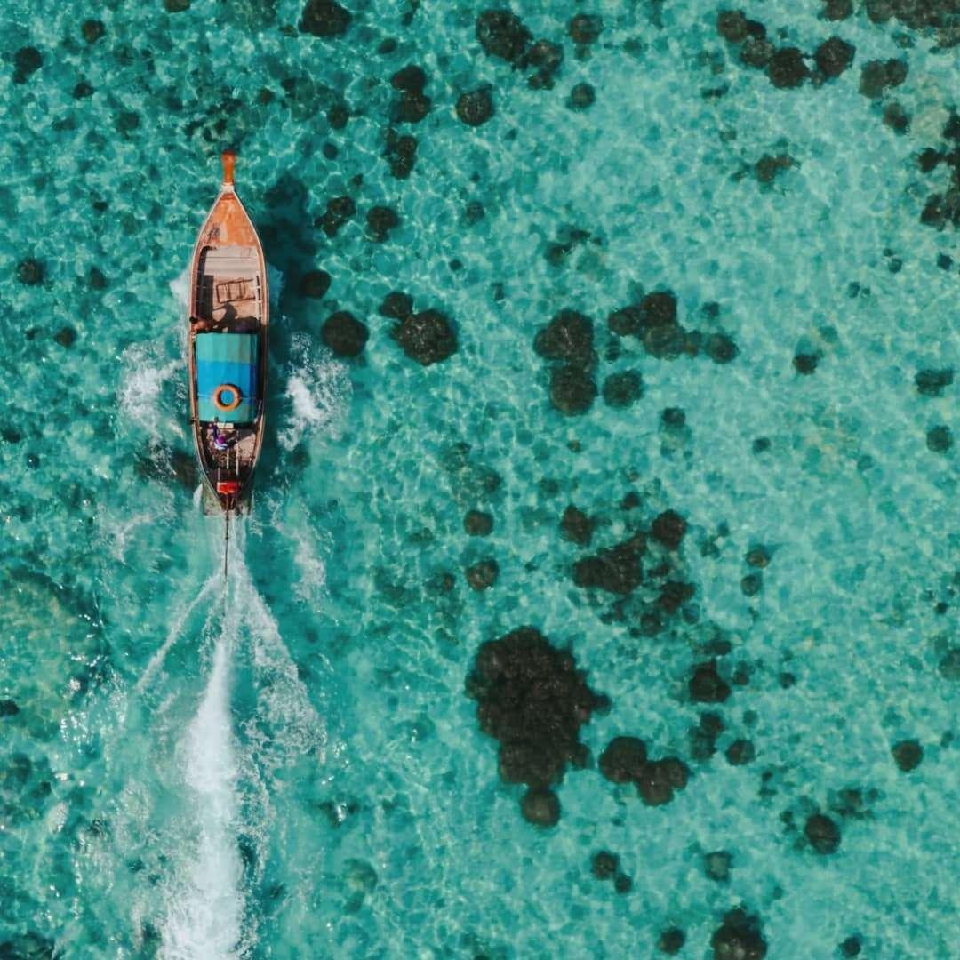 varende longtailboot gezien met de drone