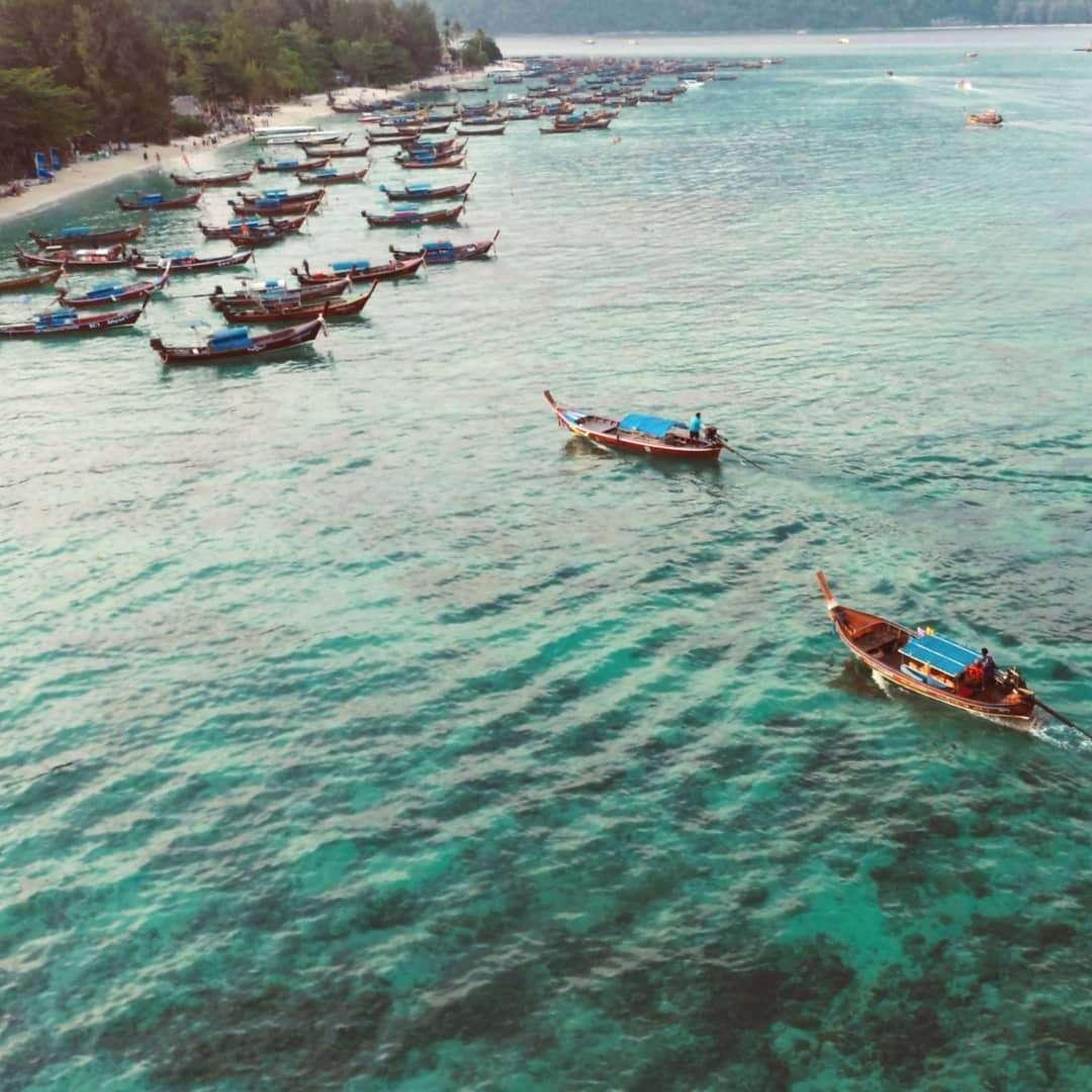 longtailboten aangemeerd aan de kust van koh lipe gezien met een drone