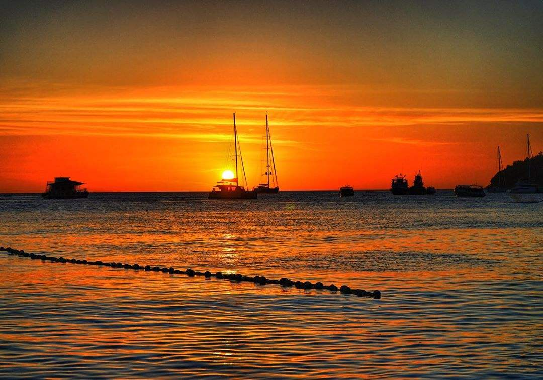 Zonsondergang op Koh Lipe met een zeilboot op de achtergrond