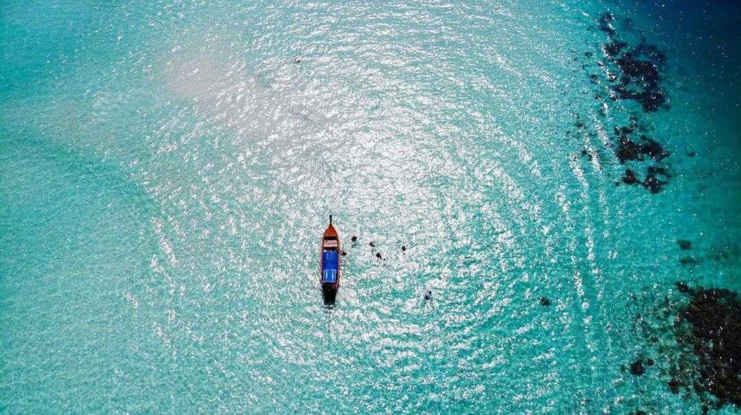 luchtfoto met longtailboot in prachtig blauw zeewater in het Tarutao National Park