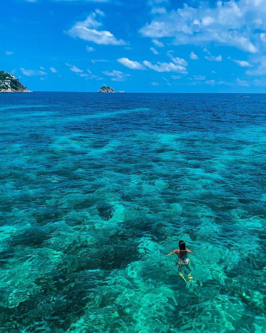 Girl swimming in the blue-green water of Koh Tao
