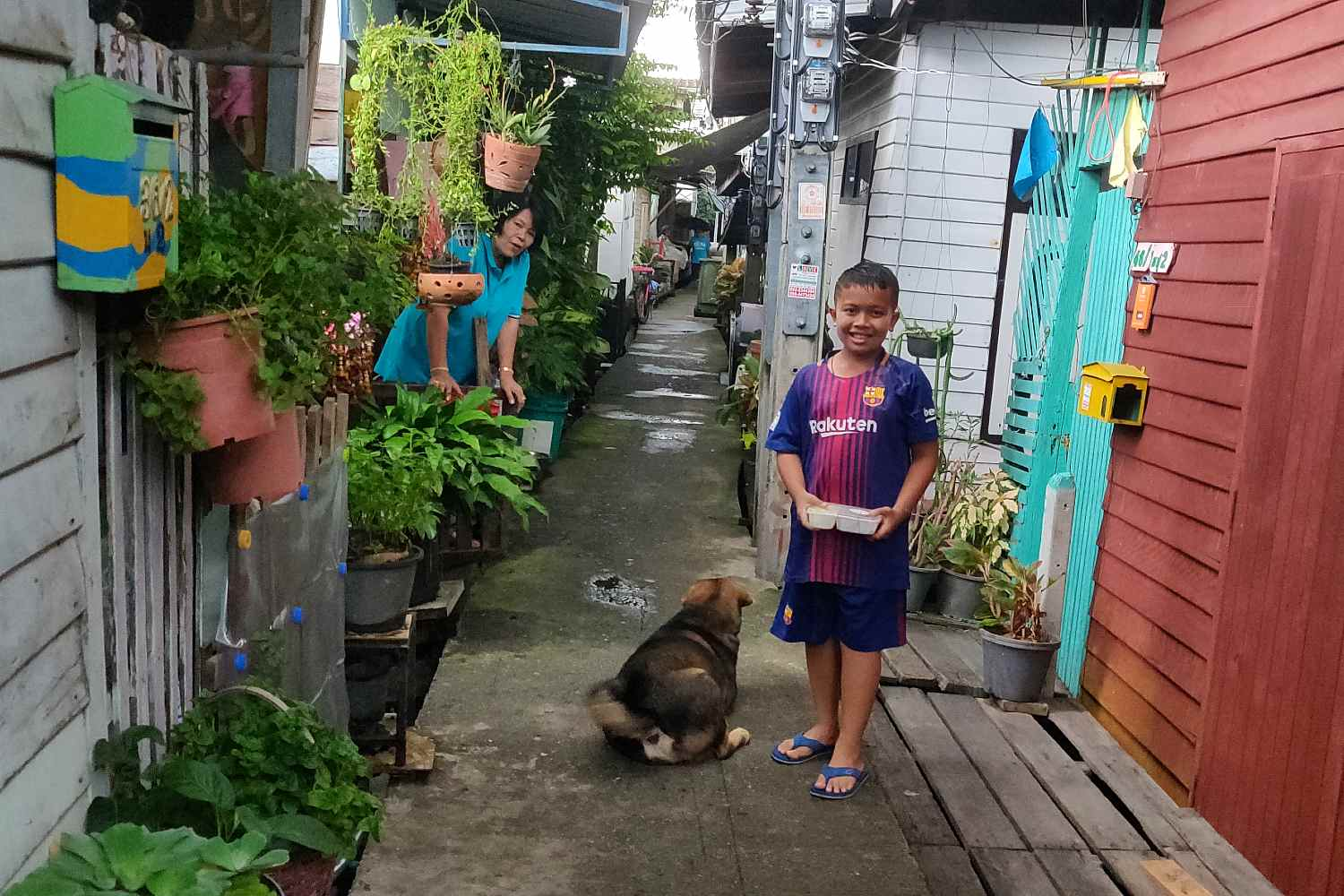 Laughing boy with dog in narrow state between wooden houses on poles