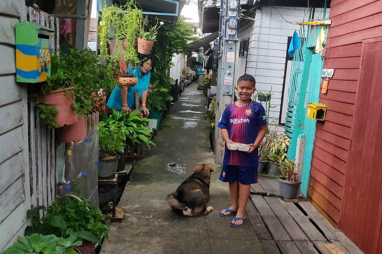 Lachende jongen met hond in smalle staat tussen houten huizen op palen